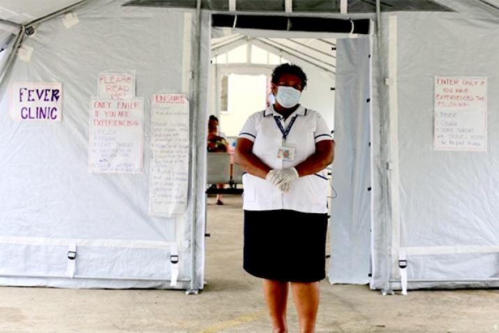 Woman with a face mask stands in front of a tent.