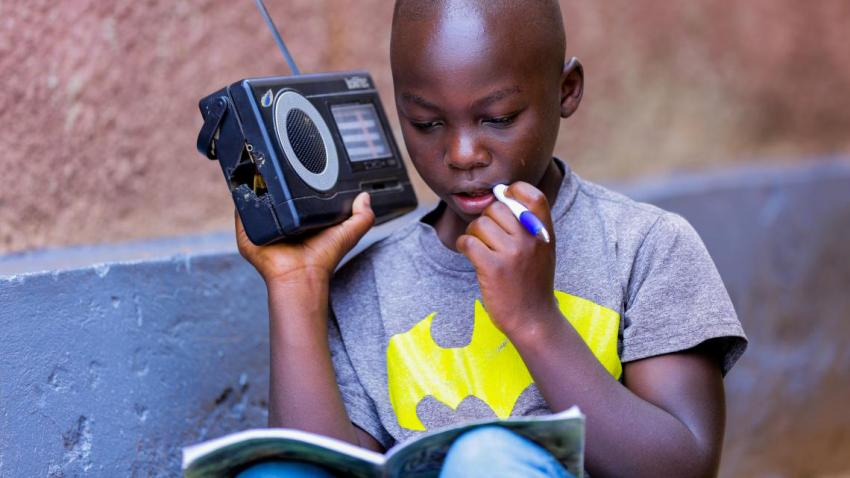 Boy holding a radio in one hand and a pencil in the other.