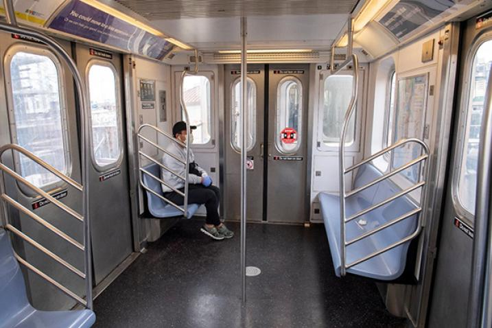 Man with face mask in empty subway car.