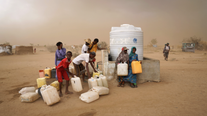 IDPs collect water during a brewing sandstorm. Water is heavily rationed and only available during one-hour windows, which normally take place just three times a day.
