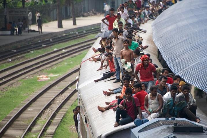 People in Bangladesh traveling dangerously on the roof of a train.