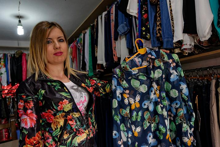 A woman holds up a blouse