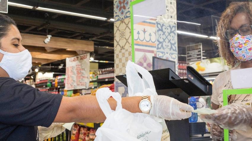 A woman with mask and gloves pays for her groceries at a supermarket
