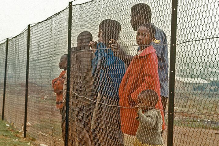 A group of South Africans behind fence separating them from white community.