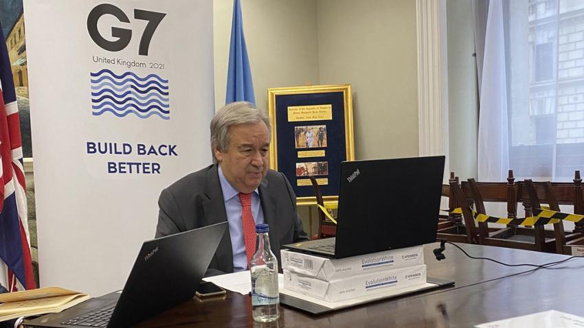 Secretary-General sits at a desk facing a laptop with the G7 on the wall behind