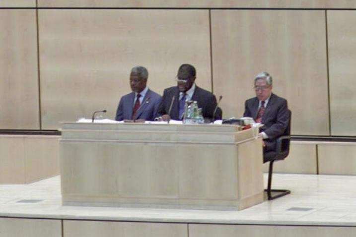 The President of the General Assembly, Theo Ben Gurirab sits at the podium with two men seated behind him on either side.