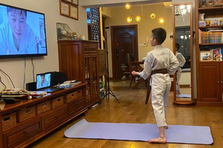 A child takes an online karate class at home