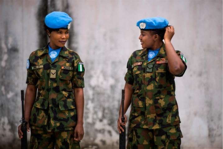 Two Nigerian peackeepers await an inspection of their base.
