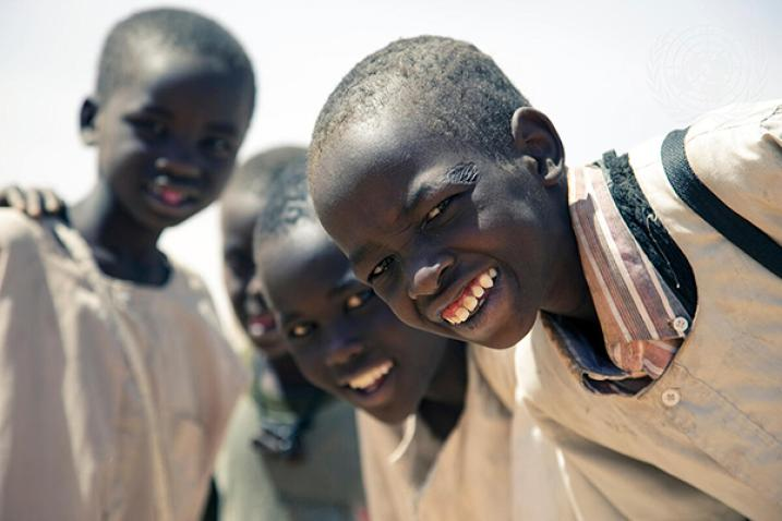 Four children in the Sudan facing camera and smiling.