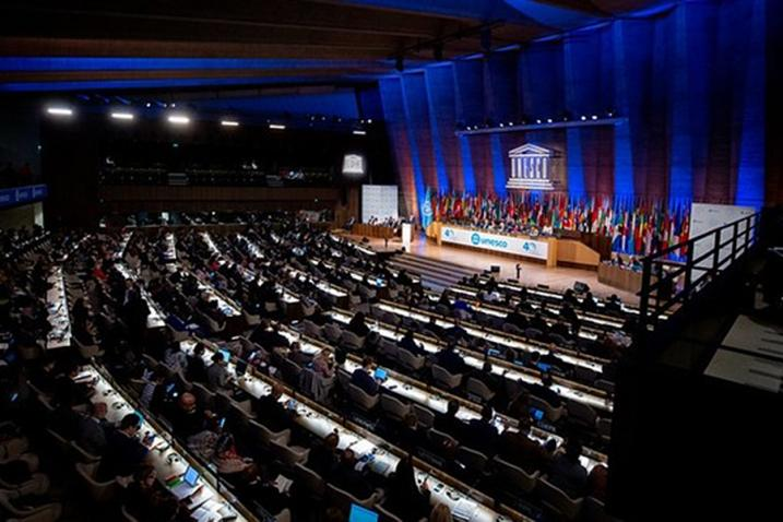 Large conference room with a stage with a row of flags in the background and the UNESCO emblem.