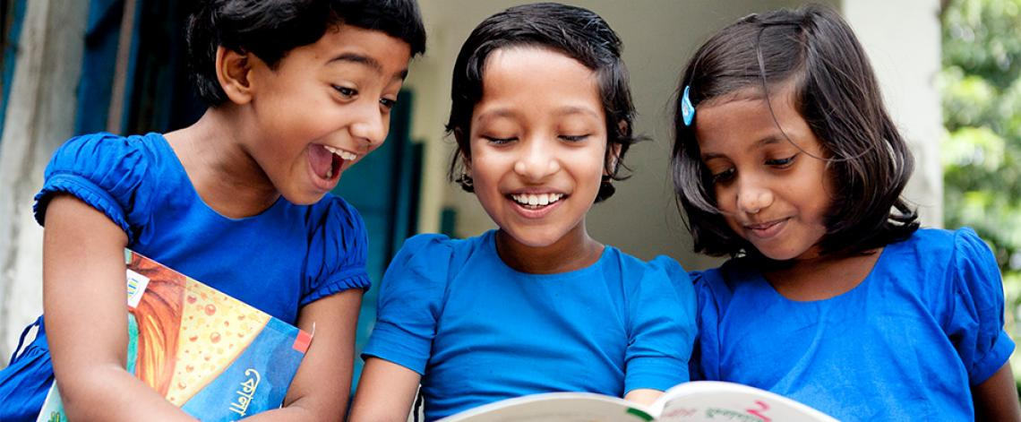 Three classmates in Bangladesh read together from a children's book provided by the non-profit organization Room to Read.