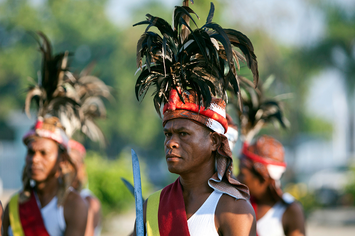Men wearing traditional head pieces line up