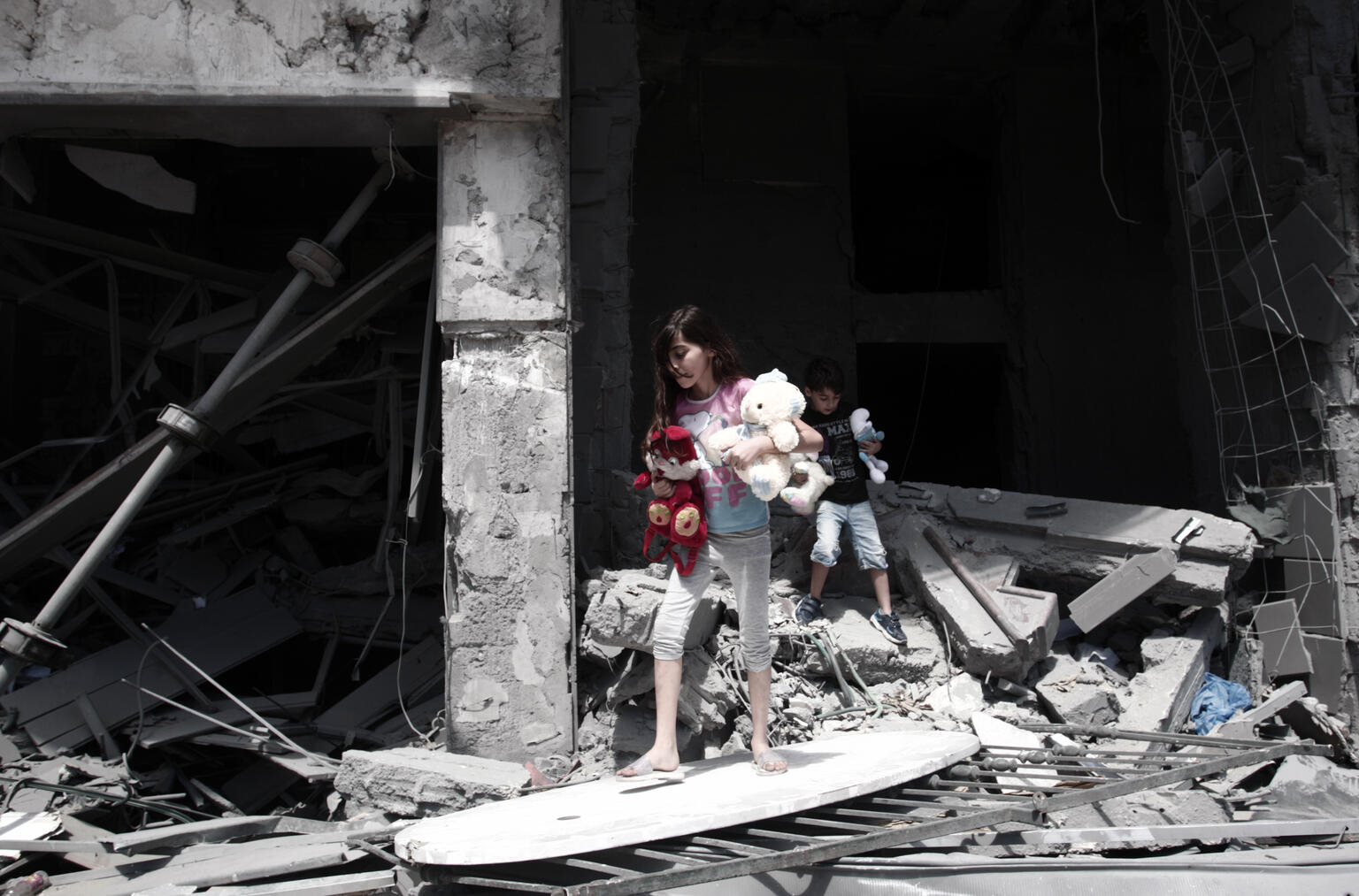 girl and boy coming out of ruins holding stuffed toys