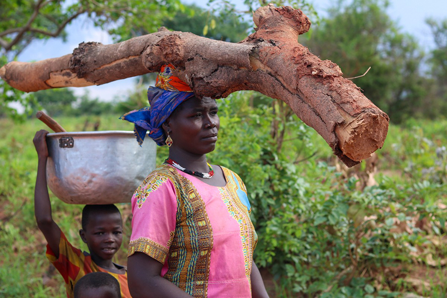 Woman walks with two boys while carrying a large log on her head.