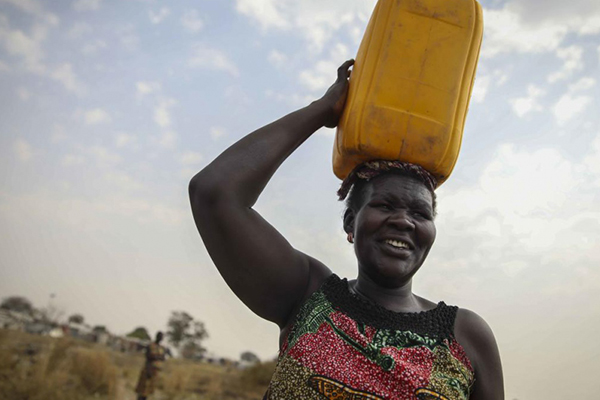 A woman carries a water jug on her head.