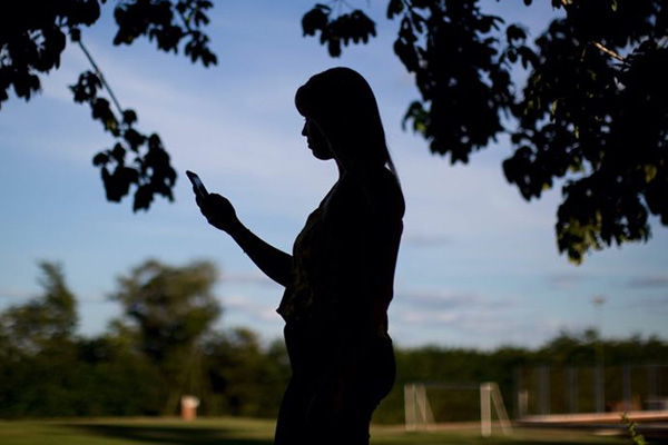 Silhouette of a woman holding a mobile phone.