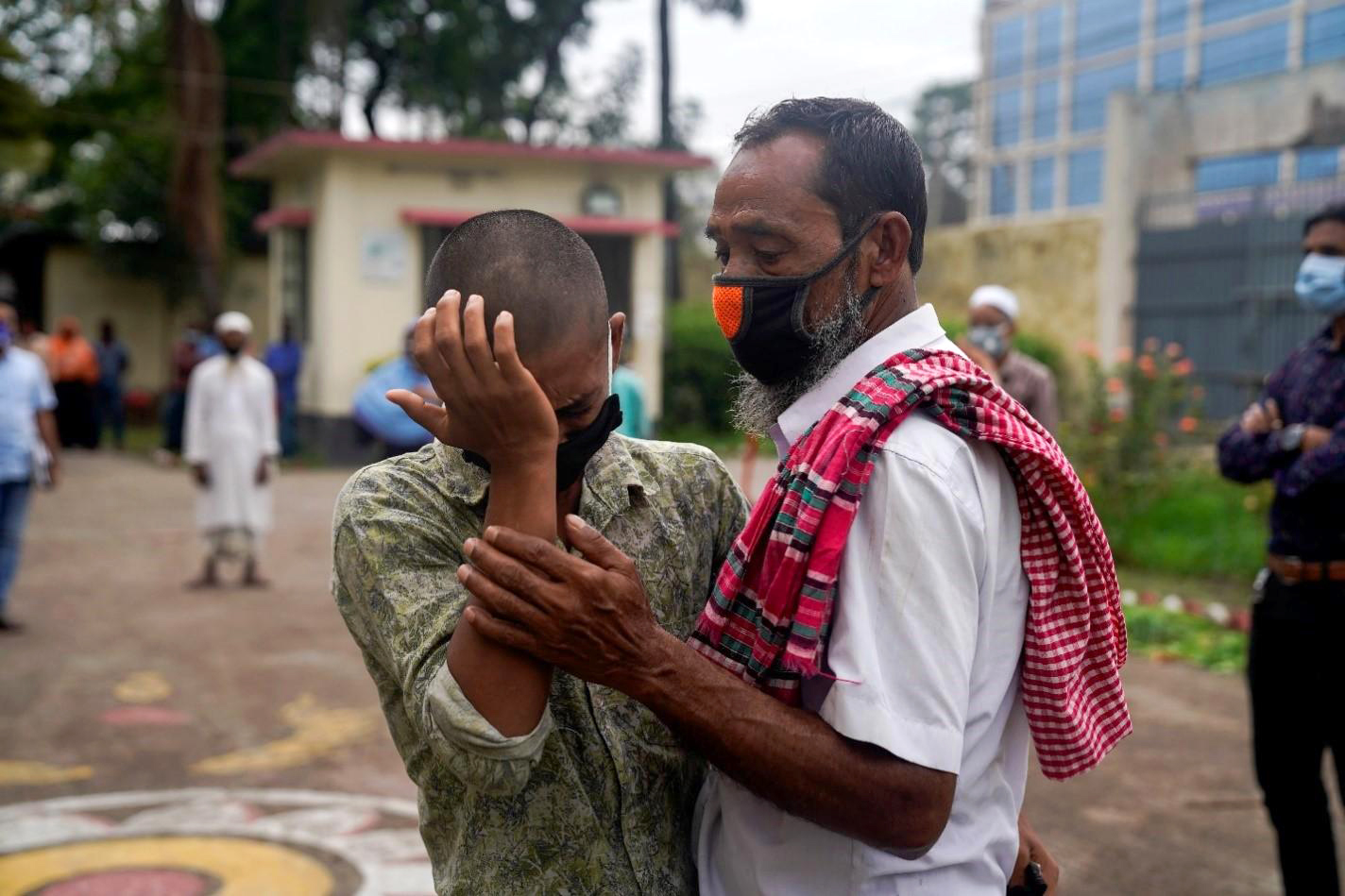An older man comforts a younger man, who is crying.