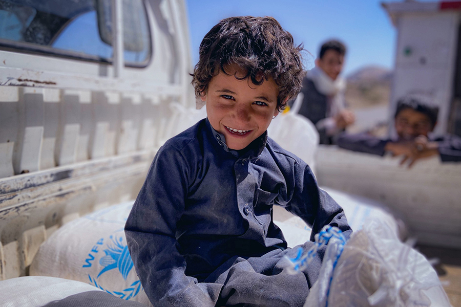 A smiling boy sits on top of sacks on a truck bed.