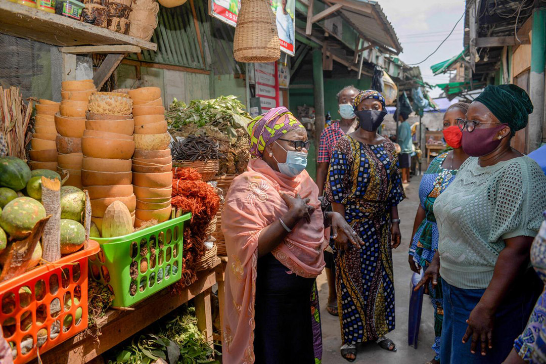women with face masks at food market having discussion