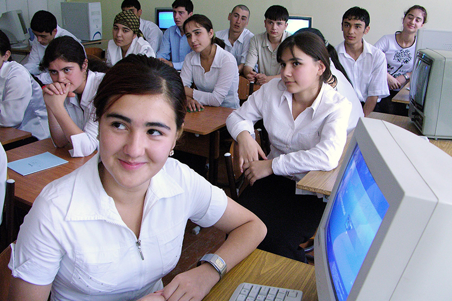 Students sit in a classroom with computers.