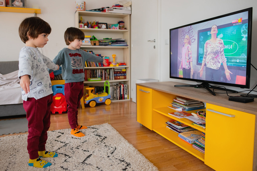 Twin brothers practice yoga as they follow a TV-classroom programme broadcast on national television.