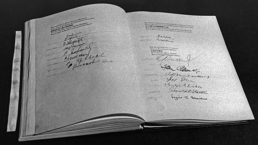 The UN Charter in 1945, opened to a signature page.