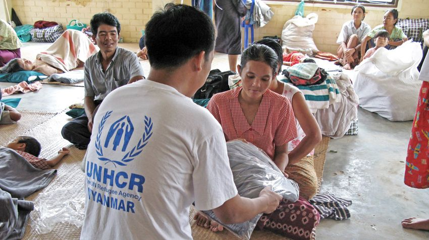 "Young Cyclone ""Nargis"" victim in Myanmar receiving a blanket from a UNHCR worker."