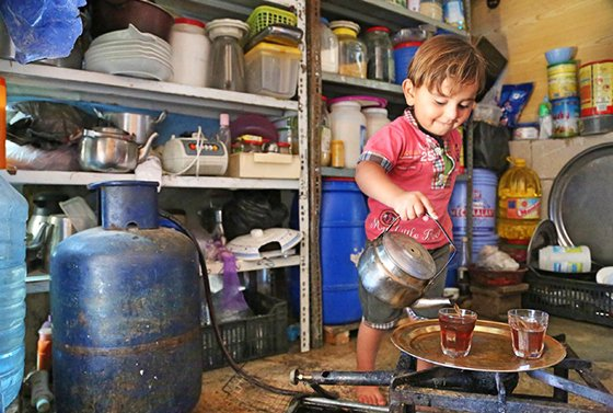 Mohamad, a young boy, pours tea in his family kitchen.
