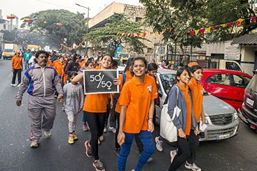 Youth dressed in orange marching against gender violence