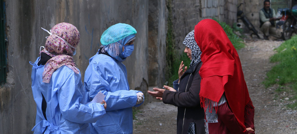 two women in face masks and protective gear taking the temperature of two other women wearing hijabs