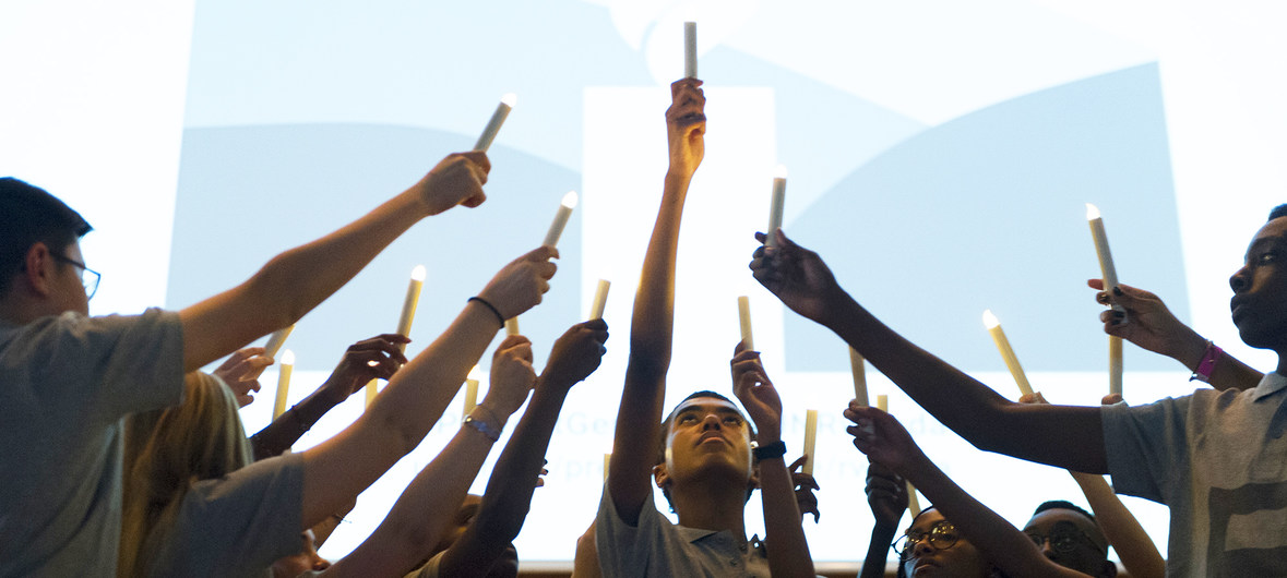 A group of people holding candles up in the air