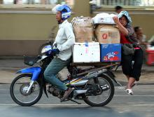 A motorcycle 'taxi' driver transports a trader and dry goods to the Phnom Penh market, Cambodia.