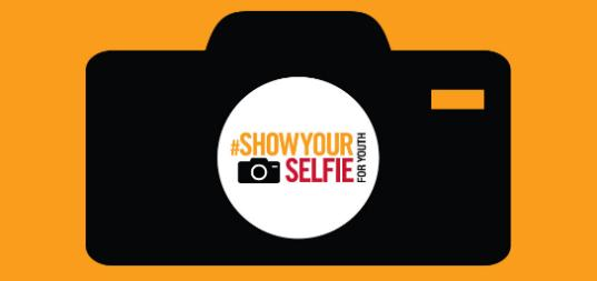 """The """"#ShowYourSelfie"""" campaign logo, which features the outline of a black camera on an orange background"""