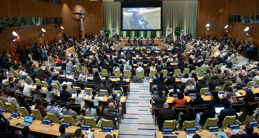 The photo shows a full council chamber at the UN Headquarters, with youth in the audience and the UN Secretary-General speaking at the front of the room, projected up on a screen.