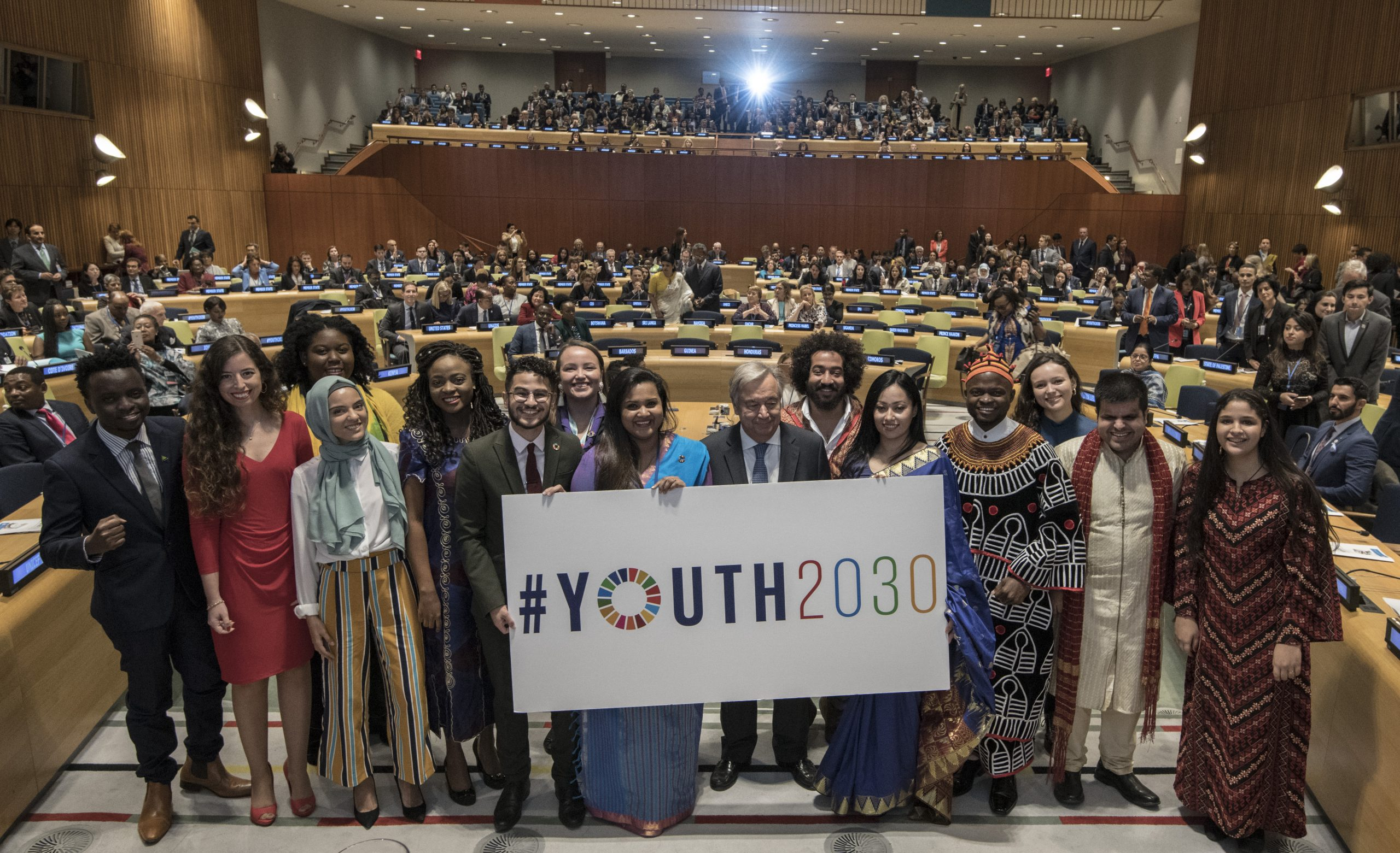Young leaders from around the world join the UN Secretary-General and the Secretary-General's Envoy on Youth in the UN General Assembly Hall. They are holding a sign that says #Youth2030.